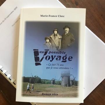 Bouquin du roman Un possible Voyage posé sur le manuscrit du livre